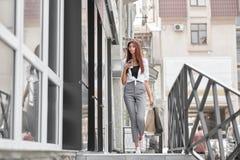 Стильная одетая девушка идя вне магазина на улице стоковые изображения