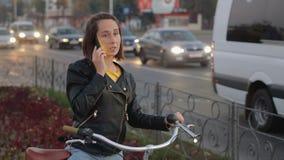 Стильная, привлекательная девушка сидя на велосипеде и говоря на телефоне на предпосылке города и автомобилей самомоднейше видеоматериал