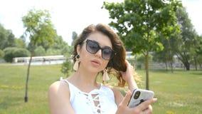 Стильная привлекательная девушка смотрит в телефон и выправляет ее волосы в парке города акции видеоматериалы