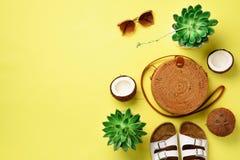 Стильная сумка ротанга, кокос, birkenstocks, succulent, солнечные очки на желтой предпосылке знамена Взгляд сверху с космосом экз стоковые фото