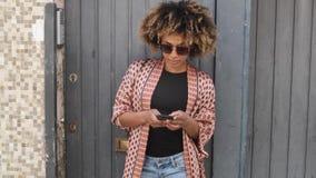 Стильная чернокожая женщина со смартфоном на улице сток-видео