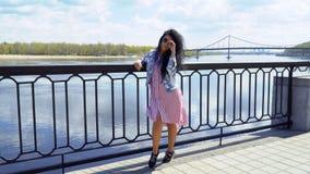 Стильное брюнет принимает ее солнечные очки стоя на обваловке реки акции видеоматериалы