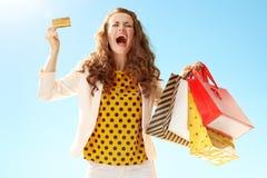 Стильное ликование покупателя и кредитной карточки женщины против bl стоковое фото rf