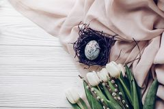 Стильное пасхальное яйцо с флористическими орнаментами в гнезде на бежевой ткани Стоковая Фотография RF