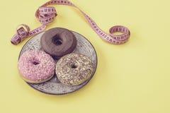 Стильное ретро блюдо с очень вкусными donuts пинка и шоколада и метром ` s портноя на желтой предпосылке диетпитание принципиальн Стоковые Фото