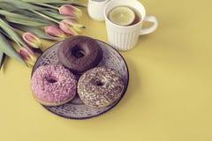 Стильное ретро блюдо с очень вкусными donuts шоколада, чашкой чаю и красивыми тюльпанами на желтой предпосылке Стоковая Фотография RF