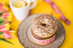 Стильное ретро блюдо с очень вкусными donuts шоколада, чашкой чаю, красивыми тюльпанами и метром ` s портноя на желтом цвете Стоковые Фото