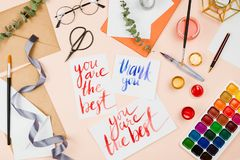 Стильное flatlay с поставками искусства, конвертами, щетками, акварелями, стеклами, ручкой и handmade карточки Стоковое фото RF