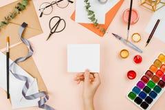 Стильное flatlay с поставками искусства, конвертами, щетками, watercolo Стоковые Фото