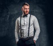 Стильно одетый молодой человек в рубашке с бабочкой и подтяжками Фото студии против темной предпосылки стены стоковое фото rf