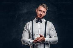 Стильно одетый молодой человек в рубашке с бабочкой и подтяжками Фото студии против темной предпосылки стены стоковое изображение rf