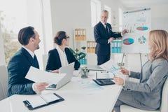 Стильные, внимательные бизнесмены сидя на столе держа бумагу Стоковое Изображение