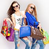 Стильные девушки с кожаными сумками в их руках на серой предпосылке стоковое изображение