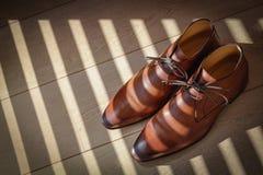 Стильные коричневые кожаные ботинки ` s людей на светлом деревянном поле стоковое фото