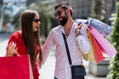 Стильные молодые пары идя с хозяйственными сумками на солнечный день Стоковая Фотография RF