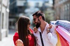 Стильные молодые пары идя с хозяйственными сумками на солнечный день Стоковая Фотография