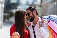 Стильные молодые пары идя с хозяйственными сумками на солнечный день Стоковое Фото