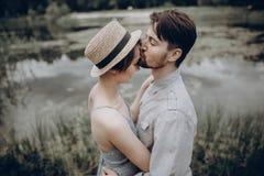 Стильные пары битника целуя на озере обнимать человека и женщины, стоковые изображения