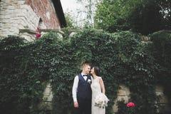 Стильные пары счастливых новобрачных идя в парк на их день свадьбы с букетом Стоковое Фото