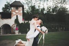 Стильные пары счастливых новобрачных идя в парк на их день свадьбы с букетом Стоковые Фотографии RF