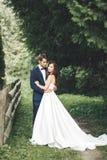 Стильные пары счастливых новобрачных представляя в парке на их день свадьбы Стоковое Изображение RF