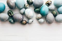 Стильные пасхальные яйца плоско кладут на белую деревянную предпосылку с космосом для текста r стоковые фотографии rf