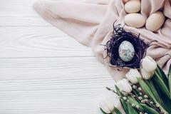Стильные пасхальные яйца с орнаментами цыпленока в гнезде на бежевой ткани Стоковые Изображения RF