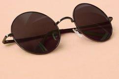 Стильные черные солнечные очки с круглыми стеклами лежат на одеяле сделанном мягкой и пушистой светлооранжевой ткани ватки модно стоковые изображения rf