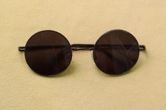 Стильные черные солнечные очки с круглыми стеклами лежат на одеяле сделанном мягкой и пушистой светлооранжевой ткани ватки модно стоковая фотография rf