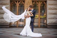 Стильные groomis идя расцеловать очаровательную невесту на предпосылке деревянных дверей Стоковые Изображения