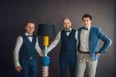 Стильные groomsmen помогая счастливому groom получая готовый в morni стоковые изображения rf