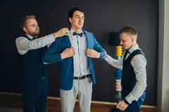 Стильные groomsmen помогая счастливому groom получая готовый в morni стоковое фото rf