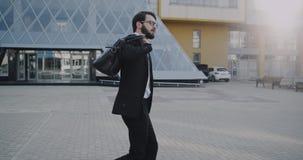 Стильный бизнесмен идя вниз с делового центра держа его портфель видеоматериал