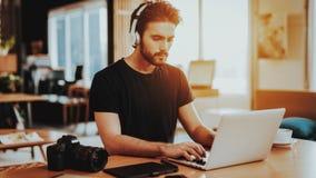 Стильный Гай в наушниках использует ноутбук на рабочем месте стоковые фотографии rf