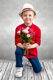 Стильный мальчик опускает на одно колено и дает букет роз стоковые фото