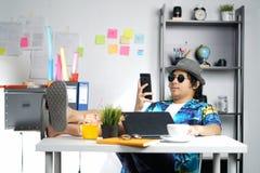 Стильный молодой профессиональный проверяя Smartphone, ноги на таблице Wh стоковое фото