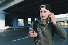 Стильный молодой человек в крышке исправляет наушники в его ушах и держит телефон позади городской архитектуры стоковое фото