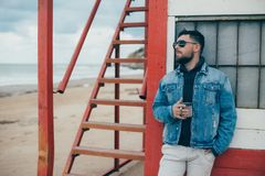 Стильный молодой человек при борода стоя близко океан с чашкой чаю Стоковая Фотография RF