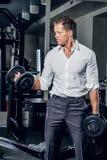 Стильный мужчина держит гантели в клубе спортзала Стоковые Фото