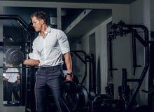 Стильный мужчина держит гантели в клубе спортзала Стоковая Фотография