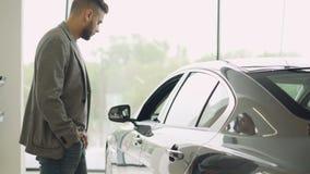 Стильный парень выбирает новый автомобиль идя вокруг роскошного автомобиля и касаясь ему в автосалоне Богатые человеки видеоматериал
