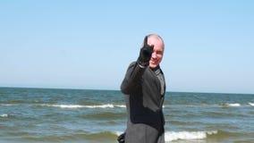 Стильный показ человека вызывает меня знаком жеста Элегантный и уверенный молодой бизнесмен на пляже Дело и перемещение акции видеоматериалы