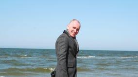 Стильный показ человека идет со мной знак и подмигивать жеста Элегантный и уверенный молодой бизнесмен на пляже развевая и акции видеоматериалы