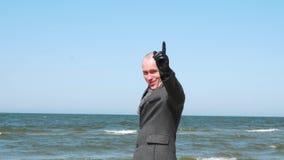 Стильный показ человека как знак, улыбка и подмигивать жеста Элегантный и уверенный молодой бизнесмен на пляже r акции видеоматериалы