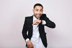 Стильный радостный молодой красивый человек в белой рубашке, черной куртке имея потеху на белой предпосылке Завоюйте успех стоковое изображение rf