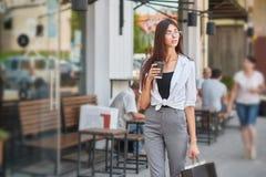 Стильный студент идя в кофе центра города выпивая стоковое изображение