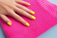 Стильный ультрамодный женский маникюр Неоновые желтые ногти на пластиковой розовой предпосылке стоковые фото