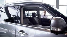 Стильный человек в белой рубашке сидит вниз в модели автомобиля для привода испытания движение медленное акции видеоматериалы