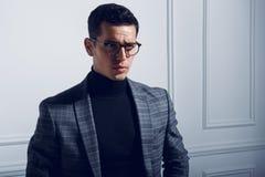 Стильный человек в костюме turtleneck, черных eyeglasses и серой куртке шотландки Горизонтальный взгляд на белой предпосылке стен стоковая фотография