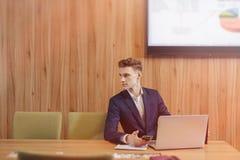 Стильный человек в куртке и рубашке сидит на столе с его коллегами и работами с документами на офисе стоковые изображения rf